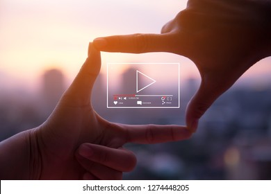 Online live video marketing concept.Photo sign made by human hands on blurred sunset sky as background - Shutterstock ID 1274448205