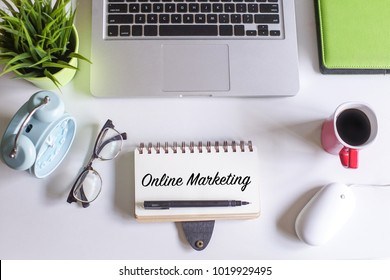 Online Marketing text written on notebook over white office table desk with laptop,spectacle.green plant,alarm clock and a cup of black coffee.Creative lay out view from top.