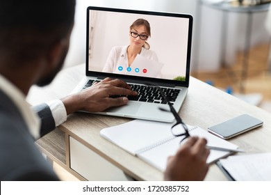 Online Meeting Concept. Back view of black male boss having video call discussion with his female colleague, copy space