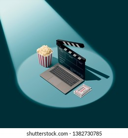 Online movie streaming and cinema: laptop with clapperboard as screen, popcorn and tickets in the spotlight