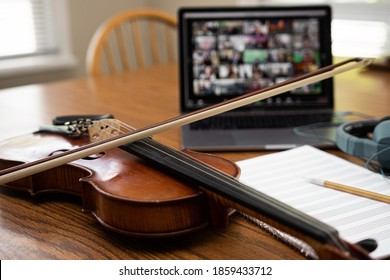 Online orchestra setup with violin, laptop computer, video conferencing