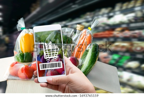 Online order grocery shopping on touch screen concept. Woman hand holding smart phone with checks the bar code or e-wallet on label for ingredient and payment. Business and technology for lifestyle.