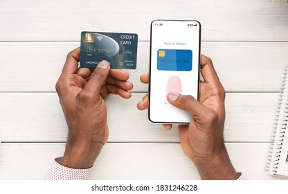 Online Payment And Biometric Identification Concept. Top Above View Of Black Man Holding Cellphone And Credit Card In Hand Showing Mobile Wallet App With Fingerprint Icon On Screen For Scanning