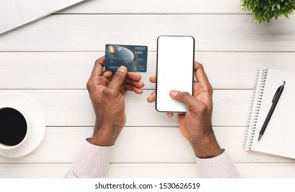 Online payment. Businessman paying his bills using smartphone with blank screen and credit card while sitting at workplace, panorama