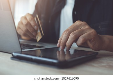 Online payment, casual man holdings credit card using digital tablet for online shopping at home with copy space. Financial technology, Fintech concept, toned. Internet purchase, e commerce concept