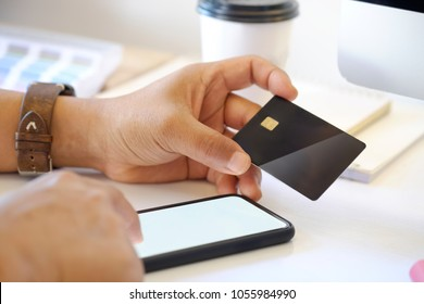 Online payment Concept. Man using credit card with mobile phone and coffee cup on white office desk.