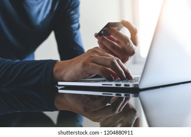 Online payment, digital banking. Man hand  using credit card for online shopping via laptop computer, close up, copy space. Cyber monday, e commerce concept
