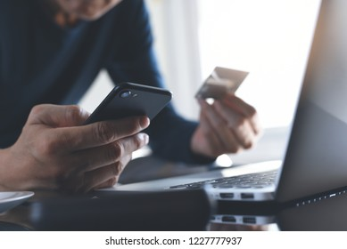 Online payment, digital banking. Man hand holding smart mobile phone, using credit card for online shopping with laptop computer and digital tablet on table. Cyber monday concept