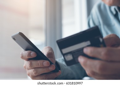 Online payment or internet banking,  man makes an online shopping by credit card payment on mobile smart phone, online banking, e commerce, e business, internet of things concept