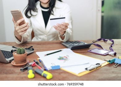 Online payment Woman  hands holding a credit card and using smart phone laptop  for online shopping  (credit and vip card concept)