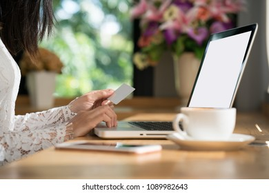 Online payment, women hands holding smartphone and using credit card for online shopping.