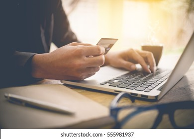 Online payment,Man's hands holding a credit card and using laptop computer for online shopping with vintage filter tone