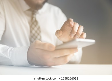 Online payments through the phone. Payment of goods online. Smartphone and Internet Commerce. Online trading on the currency exchange. Young businessman with a bank credit card in his hands.