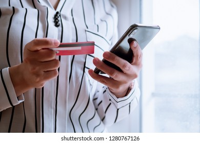 Online payment,Woman's hands holding a credit card and using smart phone for online shopping