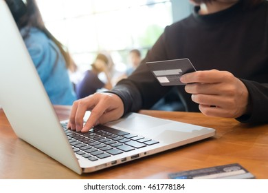 """Online payment,""""Woman's hands holding a credit card and using laptop for online shopping in coffee shop"""