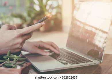 Online payment,Woman's hands holding smartphone  and using computer laptop for online shopping.