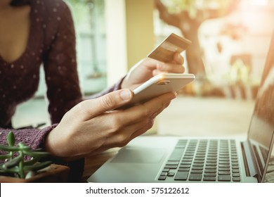 Online payment,Woman's hands holding smartphone and using credit card for online shopping.