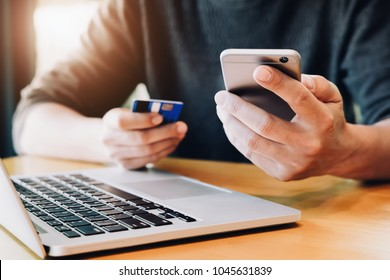 Online payment,Young Man's hands holding smartphone and using credit card and computer laptop for online shopping.  black friday or cyber monday concept.