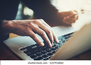 Online payment,Young Man's hands using computer and hand holding credit card for online shopping.