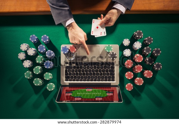 Online player's hands with laptop and stack of chips all around on green table top view, he is holding two ace cards