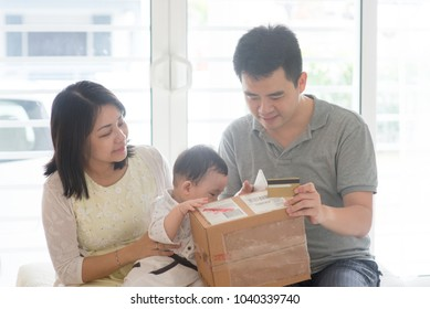 Online purchase with credit card. Happy Asian family at home, natural living lifestyle indoors.