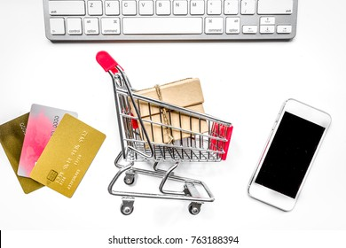 online purchasing with mini trolley, cards and phone on white de