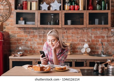 Online recipe. Cakes and pastries cooking. Young female with smartphone. Sweet homemade bakery around.
