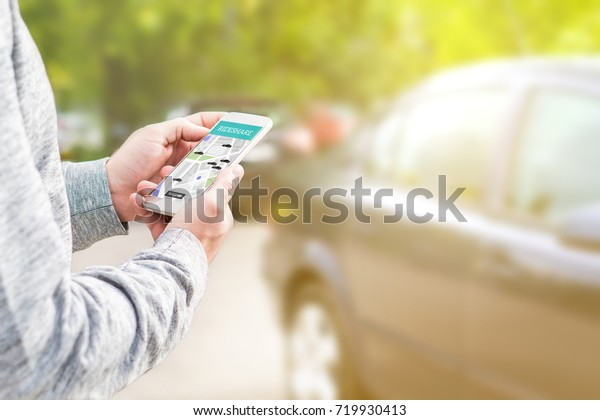Online ride sharing and carpool mobile application. Rideshare taxi app on smartphone screen. Modern people and commuter transportation service. Man holding phone with a car in background.
