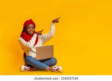 Online sales. Young african girl in winter red knitted set with laptop pointing at copy space over yellow background