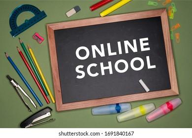 Online school written on chalkboard, stationery on green background.