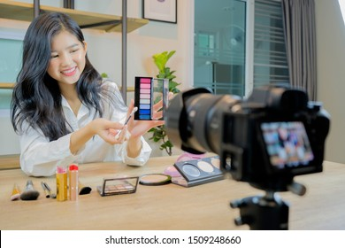 Online seller owner recording the video clip to reviewing her product for upload to website online shop. Online Selling , Online Shopping and e-Commerce concept.