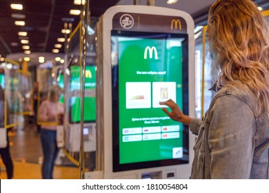 Online service McDonald's inside. The girl makes an order by touching the monitor screen. Moscow, Russia, 08/25/2020.