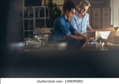 Online shop business partners working in small office together. Woman packing the purchased product in the box with man updating the shipment status on laptop.