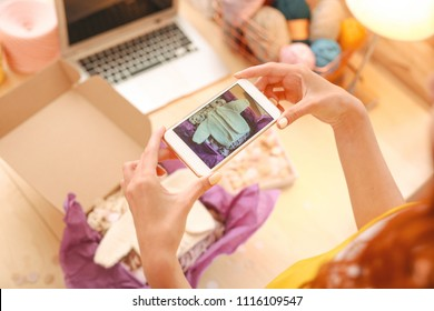 Online shop. Freelance professional needlewoman taking pictures for her prosperous famous online shop