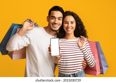 Online Shopping App. Cheerful young arab couple showing smartphone with blank white screen at camera and holding bright shopper bags while standing isolated over yellow studio background, mockup