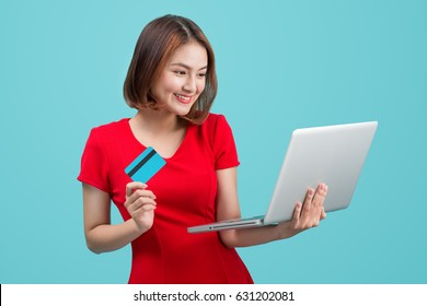 Online shopping. Asian woman holding laptop and credit card ready to pay.