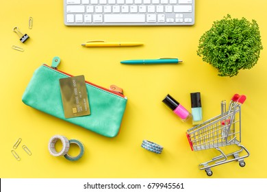 Online shopping. Bank card in purse nearby keyboard and mini shopping cart on yellow background top view - Shutterstock ID 679945561