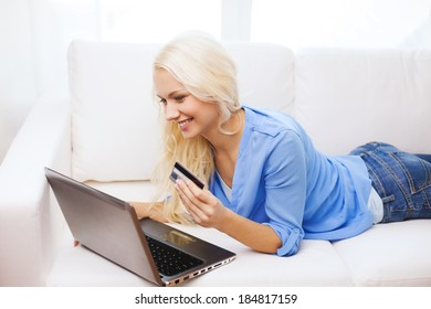 online shopping, banking and technology concept - smiling young woman with laptop computer and credit card