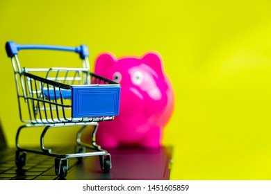 Online Shopping buyer or saving choices for choosing between shopping cart and piggy bank isolate on yellow space background