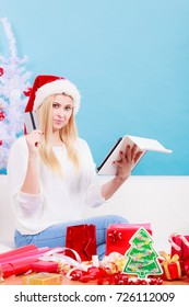 Online shopping, buying Christmas gifts on Internet concept. Woman in Santa hat sitting on sofa holding tablet and credit card, browsing net.