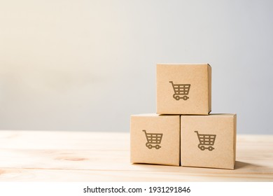 Online shopping ,Shopping cart logo on boxes on wooden table.
