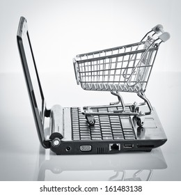 Online shopping. Shopping cart with notebook on the white. shopping cart over a laptop