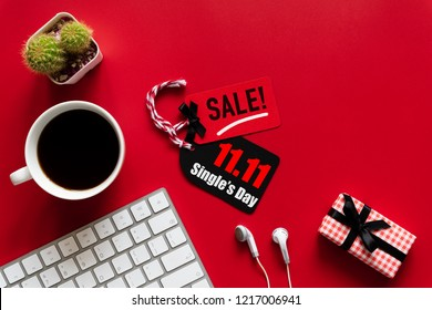 Online shopping of China, 11.11 single day sale concept. Red and black ticket with coffee cup, keyboard computer and gift box on red background. Shopping concept.