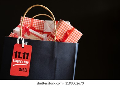 Online shopping of China single day sale concept. Shopping bag and gifts boxes with message tag.