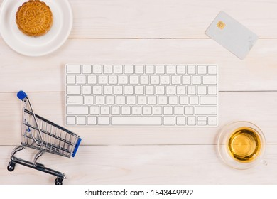 Online shopping concept. Computer keyboard, shopping cart, cake and tea with copy space.