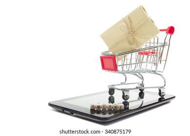 Online shopping concept - Empty Shopping Cart, laptop and tablet pc or smartphone, gift box isolated on white background. Copy space for text. Online word written on wood block.