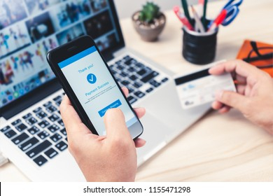 Online shopping concept, hands holding using smartphone for mobile internet banking with credit card for making payment transaction with laptop on table