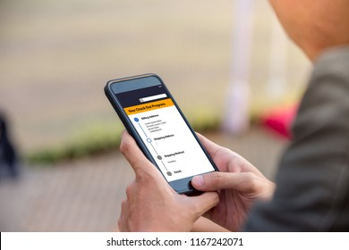 Online shopping concept. Man holding phone with online shopping app on the screen.
