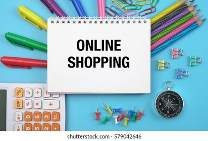ONLINE SHOPPING CONCEPT ON NOTEBOOK WITH BLUE BACKGROUND