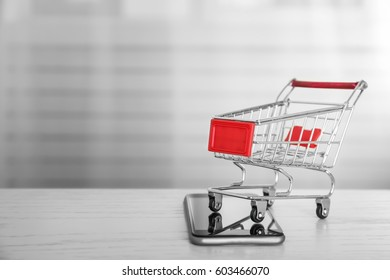 Online shopping concept. Smartphone with mini market trolley on wooden table